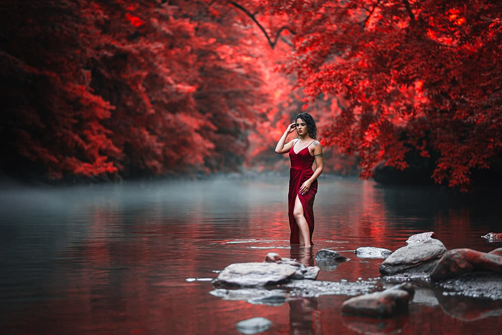 Elijah Sanchez professional photographer photography scenic rocks nature natural raw but meaningful red vibrant dress lipstick pop leaves trees river fog lake stunning beautiful woman curly wet hair tattoos standing water creative repute