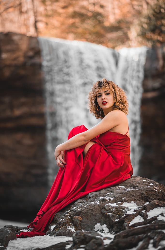 Elijah Sanchez professional photographer scenic rocks nature raw but meaningful red vibrant dress lipstick pop waterfall stunning beautiful woman curly hair gold hoop earrings creative repute