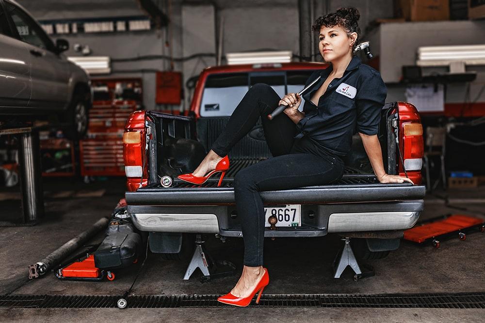 Jared Gruenwald left eyed studios professional photographer stunning woman curly brown hair red heels truck mechanic tool auto shop garage dark blue jeans creative repute