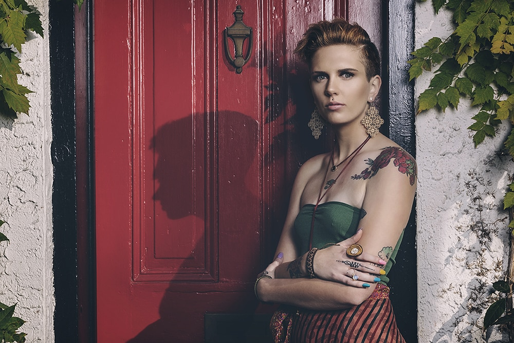 Jared Gruenwald left eyed studios professional photographer woman tattoos short hair big earrings colorful nails red door outside shadow intense gaze jewelry creative repute