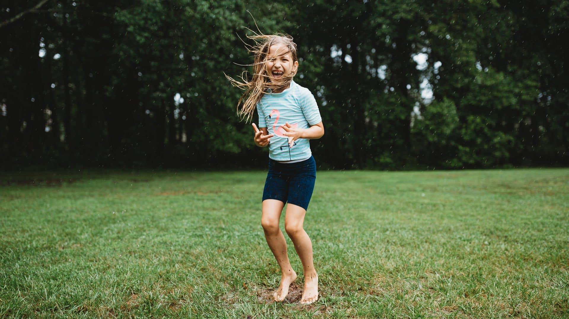 Mike Mielcarz professional photographer little girl smiling jumping rain grass bare feet woods creative repute