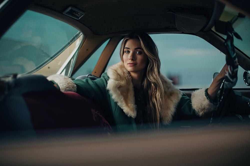 justin muir professional photographer long blonde hair elegant woman driving fur collar green coat