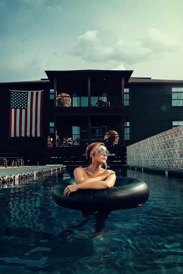 justin muir professional photographer woman floating pool blonde hair american flag sunglasses dark blue luxury creative repute