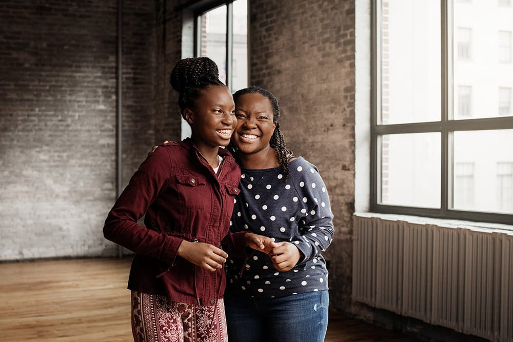 matthew stanley professional lifestyle photographer storytelling african american women hugging embracing smiling laughing beautiful bright room family friends love creative repute mother daughter sickle cell disease