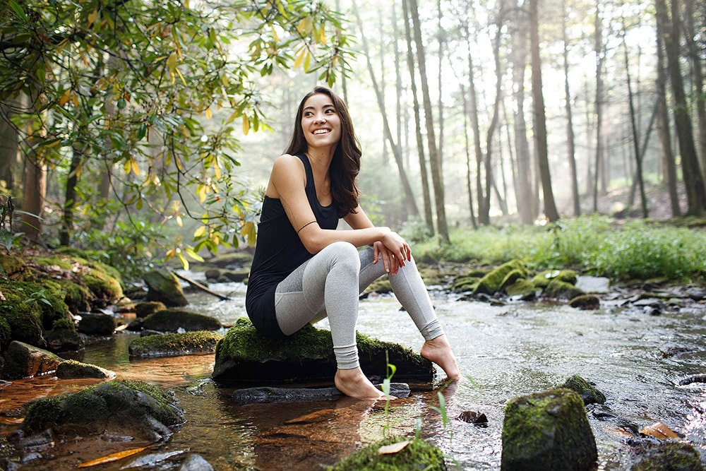matthew stanley professional lifestyle photographer storytelling asian woman natural setting river creek luscious plants barefoot long hair smiling woods grass rocks green creative repute yoga active-4238